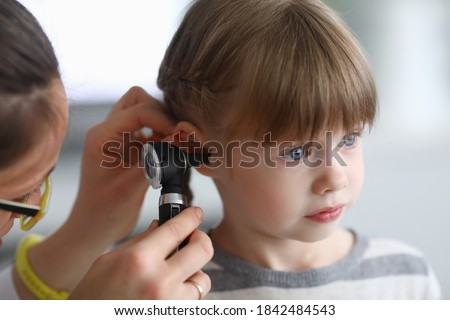 Otorhinolaryngologist examines little girl's ear with otoscope. Adenoiditis as cause of otitis media in children concept. Royalty-Free Stock Photo #1842484543