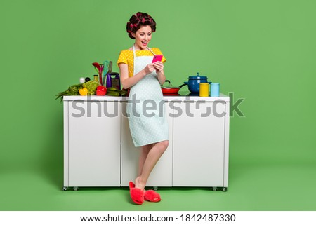 Full length body size view of her she nice attractive cheerful cheery glad mature housewife cooking dish using cell search video workshop blog blogger isolated green pastel color background