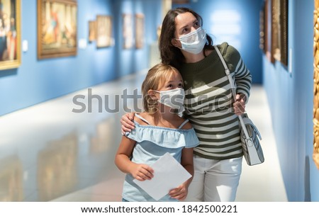 Portrait of woman with girl in medical masks standing in museum of art and looking at painting Royalty-Free Stock Photo #1842500221
