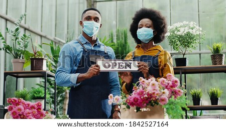Portrait of joyful African American male and female in masks standing in flower shop and holding Open sign. Woman and man florists workers looking at camera in good mood. Family business concept Royalty-Free Stock Photo #1842527164