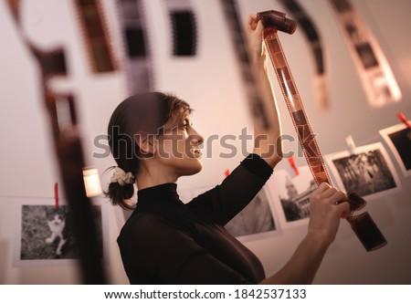 Young creative female holding filmstrip. Portrait of creative girl photographer in photo studio darkroom. Developing analog camera film