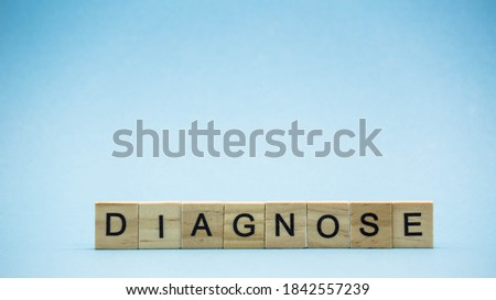 The word DIAGNOSE is written in wood letters on blue background. Pandemic coronavirus. Covid 19 Royalty-Free Stock Photo #1842557239