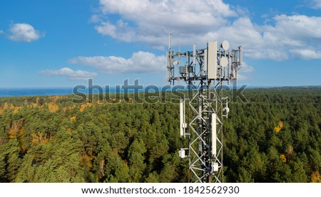 telecommunication tower with cellular antennas for 5g mobile internet network on forest and blue sky background Royalty-Free Stock Photo #1842562930