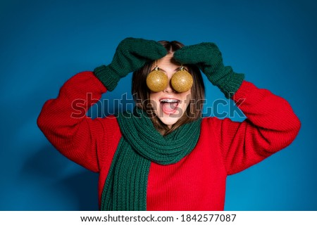 Close up portrait photo of cute playful young girl open mouth hold two baubles hiding eyes funny decorating house wear red pullover green scarf gloves isolated dark blue color background #1842577087