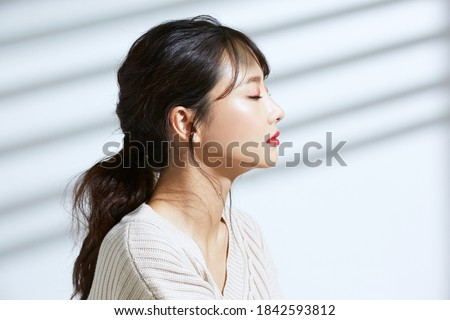 Beauty portrait of young Asian women on light and shadow background Royalty-Free Stock Photo #1842593812