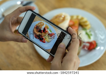 Woman's hand is taking a picture of a strawberry pancake with a smartphone. Women are taking photos to post or share popular dishes for social media.