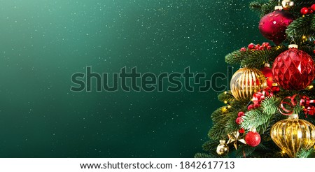 Decorated with ornaments and lights Christmas tree on dark green background. Merry Christmas and Happy Holidays greeting card, frame, banner. New Year. Noel. Winter holiday theme.  Royalty-Free Stock Photo #1842617713