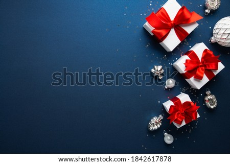 Merry Christmas and Happy Holidays greeting card, frame, banner. New Year. Noel. White Christmas gifts red ribbons, ornaments on blue background top view. Winter holiday xmas theme. Flat lay. Royalty-Free Stock Photo #1842617878