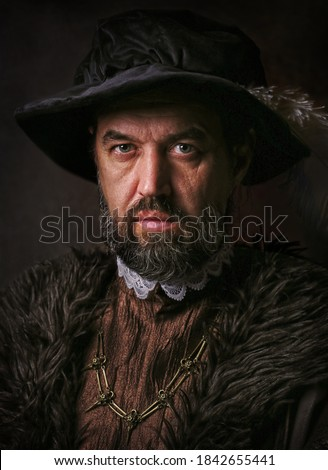Portrait of medieval young man in vintage clothing on dark background. Royalty-Free Stock Photo #1842655441