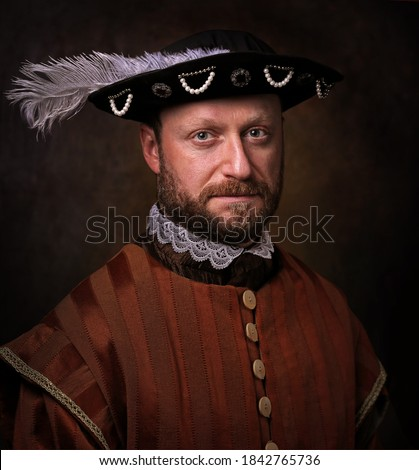 Portrait of medieval man in vintage clothing on dark background. Royalty-Free Stock Photo #1842765736