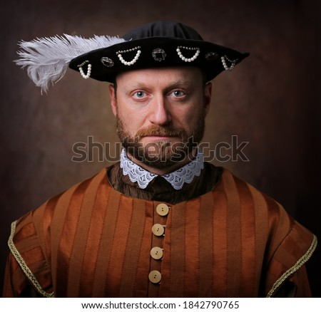 Portrait of medieval man in vintage clothing on dark background. Royalty-Free Stock Photo #1842790765