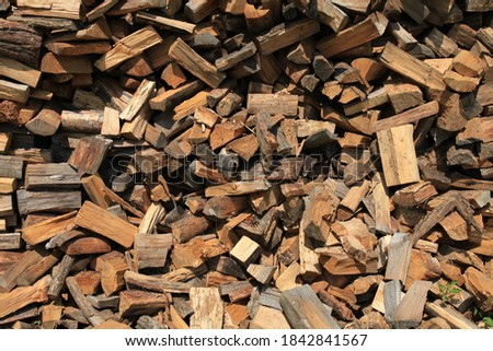 Firewood. Alternative and cheap energy source for heating. Heating season. Background and texture of wooden logs. Wooden fuel. Stock of renewable resources for the winter when energy prices rise