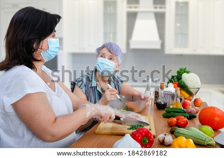 Even the pandemic could not cancel the weekly joint cooking of a vegetable salad by a caregiver and old lady. Only both are wearing protective face masks now. Royalty-Free Stock Photo #1842869182