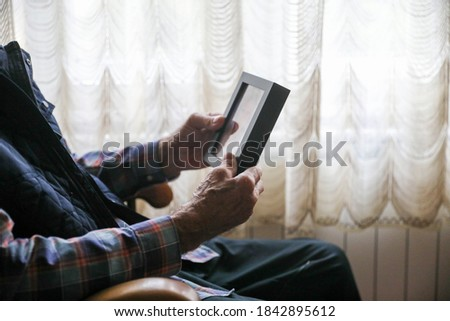 Senior Man Looking At Family Portrait Holding Photo Frame Sitting On Sofa At Home. Selective Focus