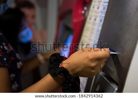 Detail photograph of a woman buying a ticket in the automatic subway machine.