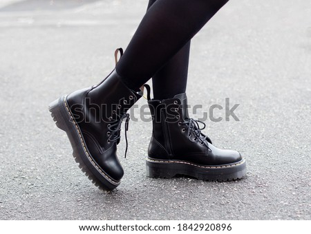 Female legs in fashion and stylish boots on grey street background Royalty-Free Stock Photo #1842920896