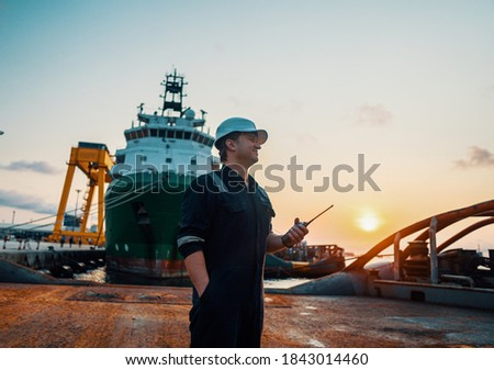 Marine Deck Officer or Chief mate on deck of offshore vessel or ship , wearing PPE personal protective equipment - helmet, coverall. He holds VHF walkie-talkie radio in hands. Royalty-Free Stock Photo #1843014460