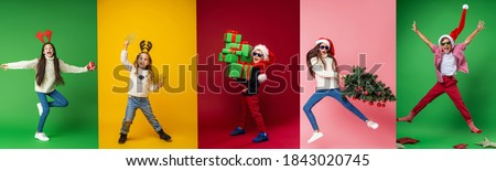 Merry Christmas! Happy children in full growth in a Santa hat, reindeer horns with gifts, Christmas tree and stars on a multi-color background, collage. Green, yellow, red, pink backgrounds Royalty-Free Stock Photo #1843020745