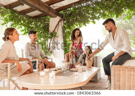 Mixed race group of friends celebrating birthday of young Hispanic woman in the garden with fruit, snacks and white wine - Happy hour in outdoor stylish ambient - Selective focus on curly brunette