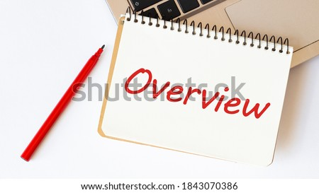 Laptop, red pen and notepad with text OVERVIEW in the white background Royalty-Free Stock Photo #1843070386