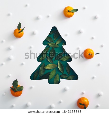 Christmas minimal concept - xmas tree silhouette made with green leaf, snow and tangerine pattern. Square composition, flat lay, view from above. Creative christmas composition.