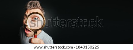 man see through magnifying glass on the black backgrounds. Big man eye Royalty-Free Stock Photo #1843150225