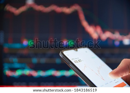 Investor analyzing stock market investments on a smartphone. Person trading stocks on a smartphone. Falling share prices at the stock exchange. Stock market crash. Trader at the stock exchange. Royalty-Free Stock Photo #1843186519