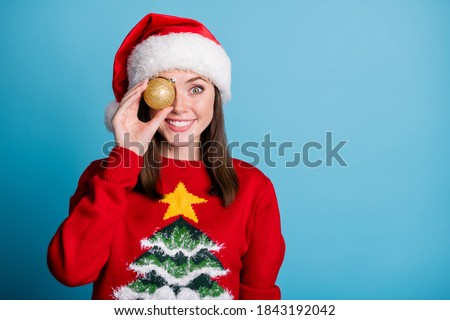 Photo portrait of woman holding golden christmas bauble near eye isolated on pastel light blue colored background with copyspace #1843192042