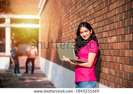 Asian Indian college student in focus working on laptop or reading book while other classmates in the background, outdoor picture in university campus