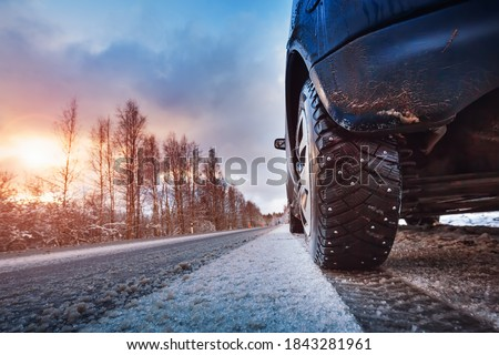 Car tires on winter road covered with snow. Vehicle on snowy way in the morning Royalty-Free Stock Photo #1843281961