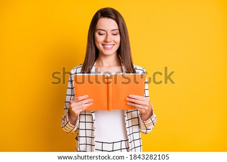 Photo of smiling shiny toothy clever lady reading book wear plaid outfit isolated yellow color background