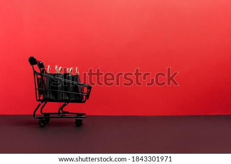 black paper bags in shopping cart on red background, copy space. black friday concept
