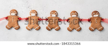 Stay home quarantine from Covid-19. Christmas gingerbread men with a masks #1843315366