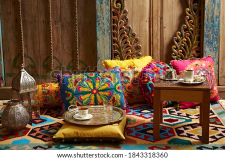 carved wood design pillows embroidered with fluorescent colors in front of the wall oriental corner turkish coffee presentation Royalty-Free Stock Photo #1843318360