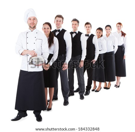 Large group of waiters and waitresses standing in row. Isolated on white Royalty-Free Stock Photo #184332848