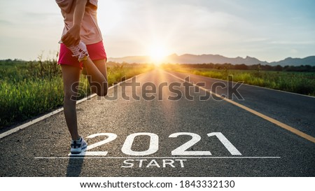 New year 2021 or start straight concept.word 2021 written on the asphalt road and athlete woman runner stretching leg preparing for new year at sunset.Concept of challenge or career path and change. Royalty-Free Stock Photo #1843332130