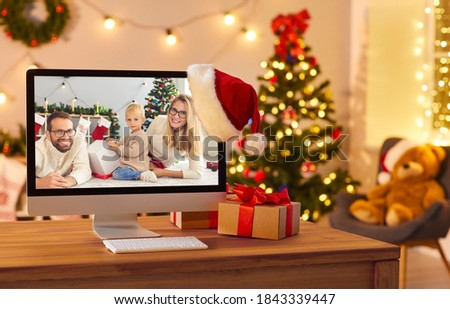 Getting together with family is the best gift. Computer on table in cozy room, with happy mom, dad and child opening Christmas presents on screen. Video call picture, staying in touch online concept