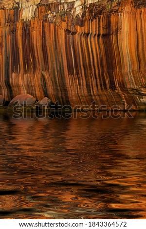 Landscape of mineral stained cliff and interesting reflections along the eroded sandstone shoreline of Lake Superior, Pictured Rocks National Lakeshore, Michigan's Upper Peninsula, USA
