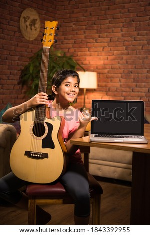Asian Indian child learning music or musical instrument online using laptop computer or tablet at home, persuing hobby
