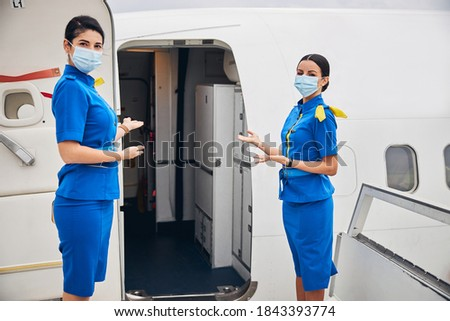 Front view of two slim female flight attendants standing at the entrance to the airplane #1843393774