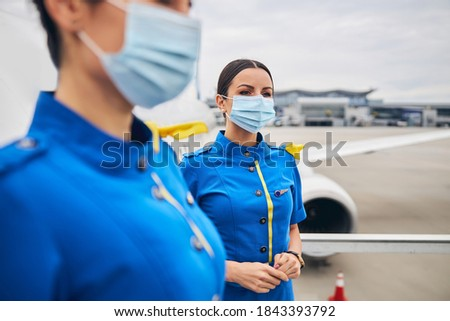 Two Caucasian female flight attendants in disposable medical masks standing on the passenger boarding stairs #1843393792