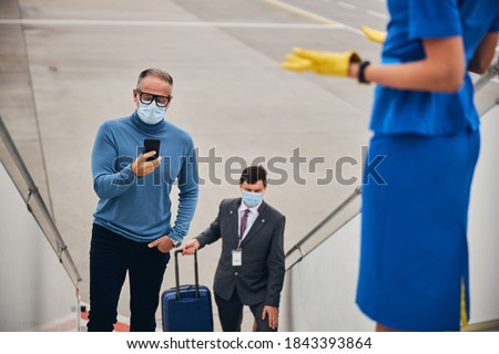Focused businessman with the cellphone standing on the boarding stairs accompanied by the airline staff #1843393864