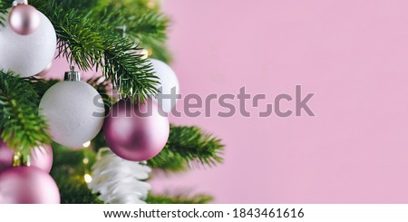 Banner with Christmas tree decorated with white and pink seasonal tree ornament baubles on pink background with empty copy space Royalty-Free Stock Photo #1843461616