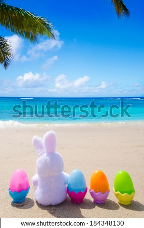 Easter bunny and color eggs on the sandy beach by the ocean #184348130