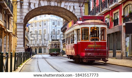 Lisbon, Portugal. Vintage red retro tram on narrow bystreet tramline in Alfama district of old town. Popular touristic attraction of Lisboa city. Public tramways trasport. Royalty-Free Stock Photo #1843517773