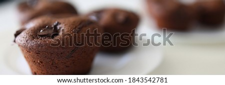 Close-up of tasty dessert for tea or coffee. Chocolate brownies with cocoa stuffing on white plate. Homemade cupcakes with crispy top. Bakery and confectionery concept