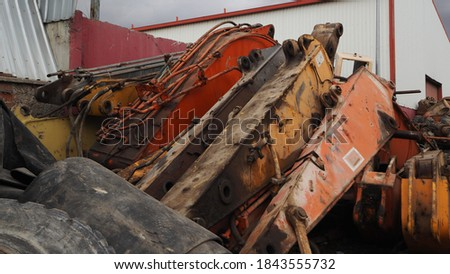 Heavy machinery scrap yard. Parts of excavators and heavy excavation vehicles that have reached the end of their useful life. Buckets, gear sets, tracks, shock absorber springs and flywheel gears. Royalty-Free Stock Photo #1843555732