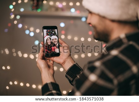 Handsome European brunette man in Christmas hat chatting on the phone with family, friends. Celebration, distance, quarantine, at home, coronavirus, video chat, online, internet, party, gift, bokeh Royalty-Free Stock Photo #1843571038