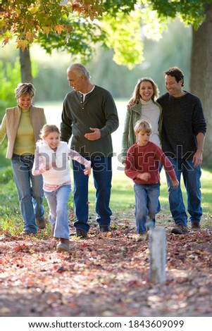 Full length portrait of a multi-generational family walking in a park with couples in embrace and children sprinting ahead during a sunny day in autumn. Royalty-Free Stock Photo #1843609099
