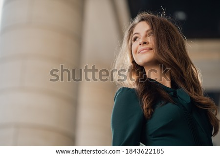 portrait of confident eye, strong nature poses of a happy young female student Caucasian appearance brunette in a green dress, turns around looking to the side Royalty-Free Stock Photo #1843622185